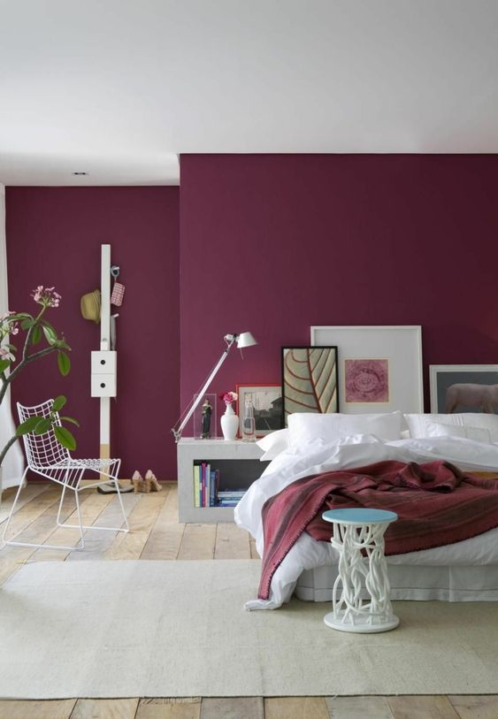 a spacious contemporary bedroom with purple walls, stylish catchy furniture, a bold gallery wall at the headboard