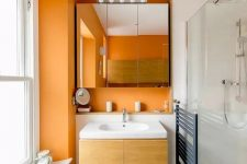 11 a stylish contemporary bathroom in white and orange, with a floating vanity and a mirror cabinet plis white tiles in the shower