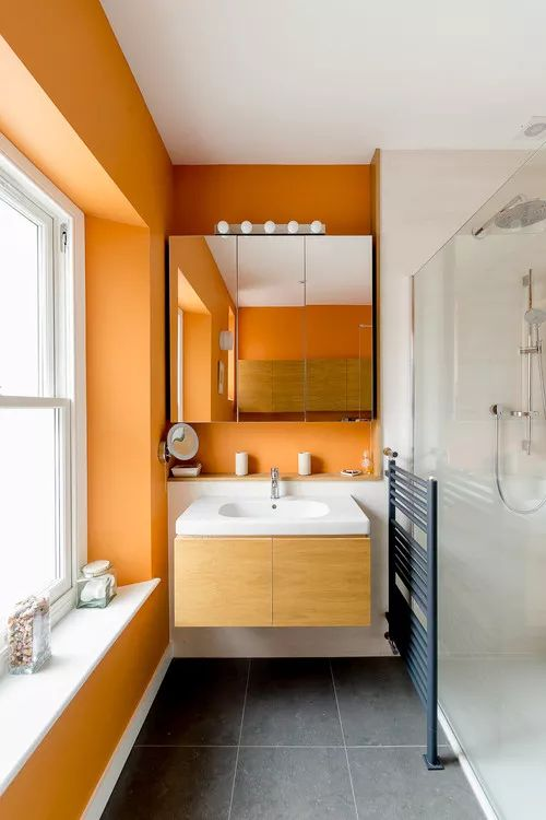 a stylish contemporary bathroom in white and orange, with a floating vanity and a mirror cabinet plis white tiles in the shower