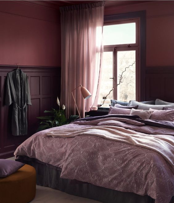 an exquisite monochromatic bedroom with burgundy and purple paneled walls, purple and lilac textiles, a pink lamp and a mustard ottoman