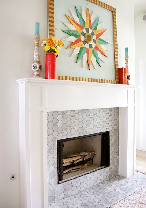 a built-in fireplace with marble hex tiles around it and on the floor and a stylish white frame and mantel