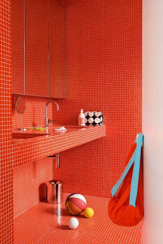 a super bold burnt orange bathroom fully clad with small scale tiles all over is ultimate