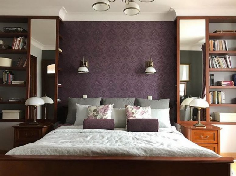 a vintage-inspired bedroom with a purple printed wall and pillows, chic stained furniture and tall mirrors plus elegant sconces