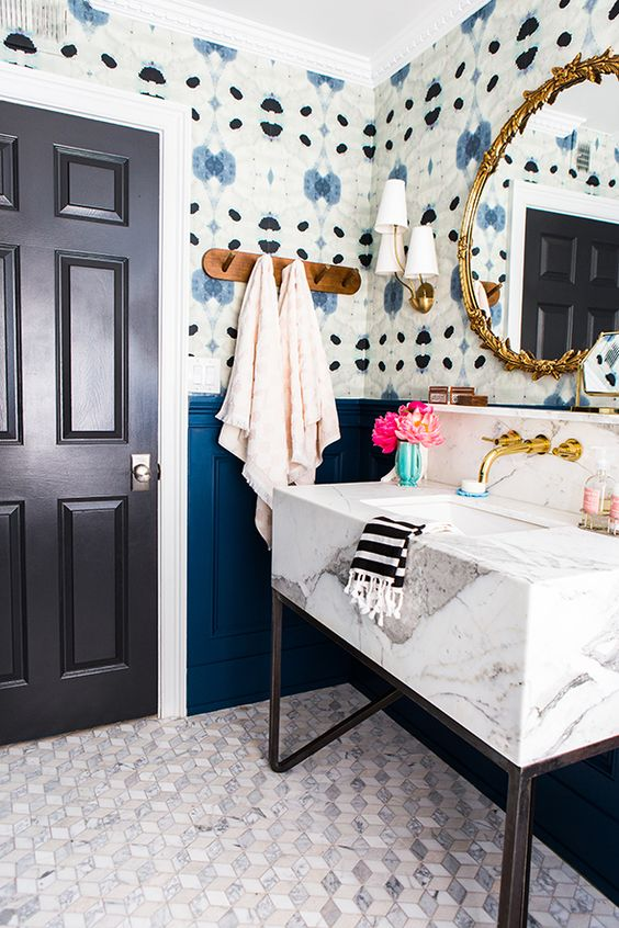 bold abstract wallpaper makes the powder room catchier and echoes with bright blue panels on the walls