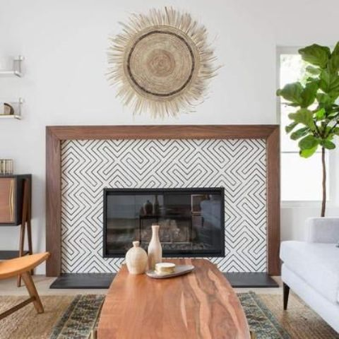 a built in fireplace with monochromatic graphic tiles around it and a rich stained wooden frame