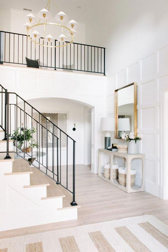 a stylish entryway lit up with chic neutral wood floors and the same cover on the stairs