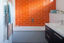 13 a stylish modern bathroom with an orange tile accent wall, a dark brown vanity and white appliances