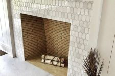 14 a built-in non-working fireplace clad with metal elongated hex tiles and with a white wooden frame