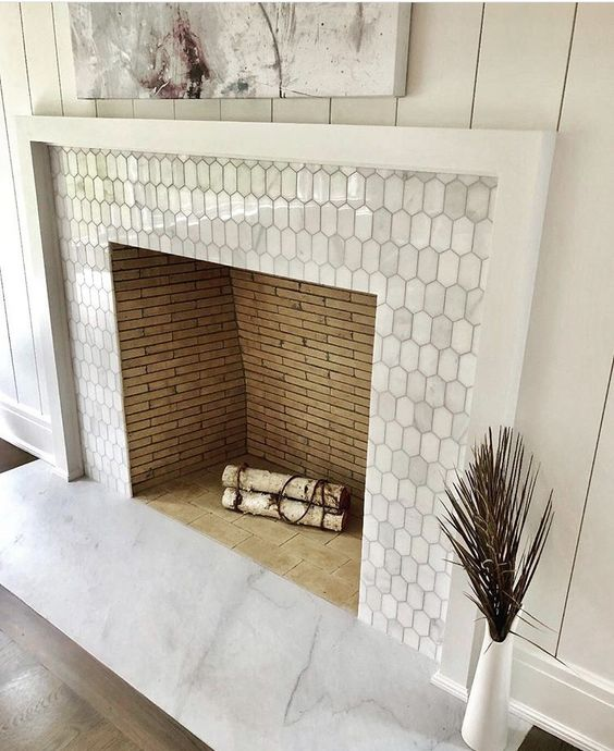 a built-in non-working fireplace clad with metal elongated hex tiles and with a white wooden frame