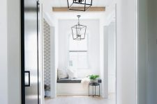 14 a corridor with a reading nook by the window lit up with light wooden floors and natural light, too