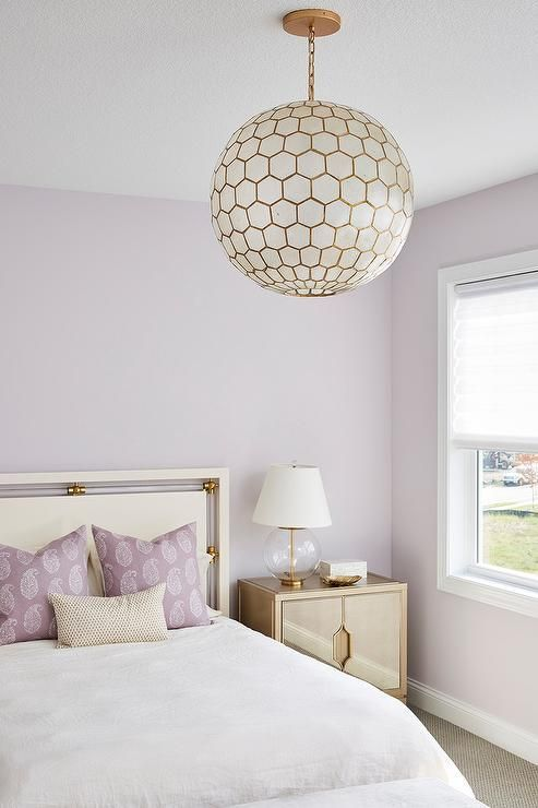 a romantic bedroom with lilac walls and pillows and tan and grey decor, with a sphere faceted lamp and a tan nightstand