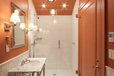 14 an elegant burnt orange, black and white bathroom with a marble sink and a mosaic floor and some chic lamps