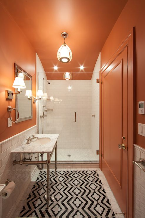 an elegant burnt orange, black and white bathroom with a marble sink and a mosaic floor and some chic lamps