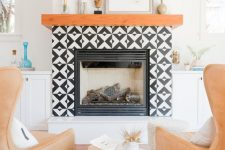 15 a faux fireplace with black and white graphic tiles clad around and a rich-stained wooden mantel