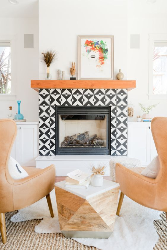 a faux fireplace with black and white graphic tiles clad around and a rich-stained wooden mantel