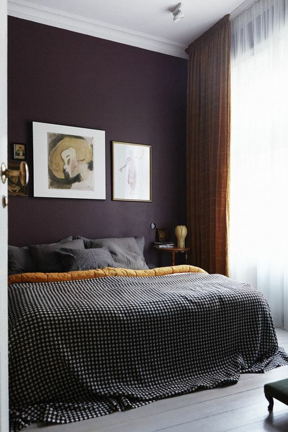 a sophisticated moody bedroom with a deep purple accent wall, musard and grey textiles and a stylish gallery wall