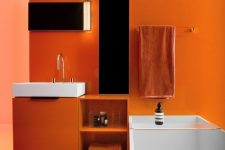 15 a super bold orange bathroom with white appliances and mirrors with lights, orange towels is mood-raising