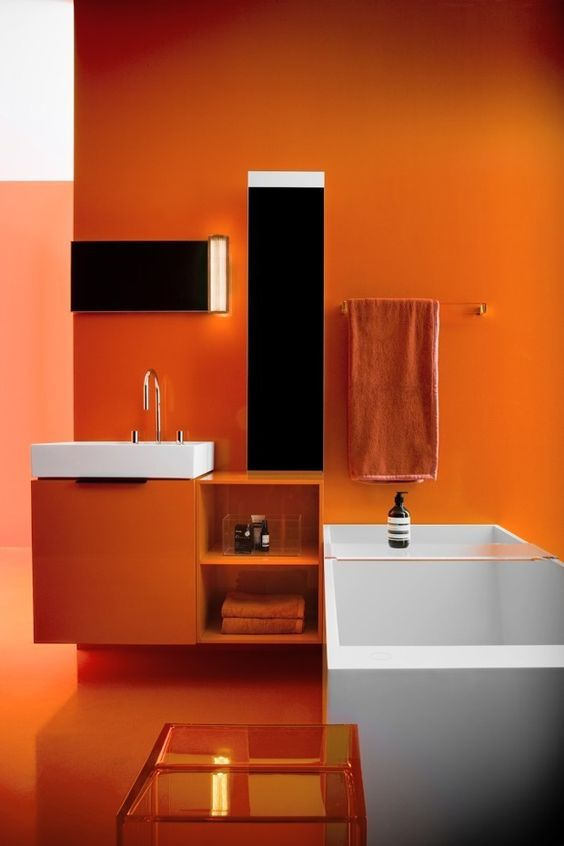 a super bold orange bathroom with white appliances and mirrors with lights, orange towels is mood-raising