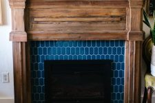 16 a faux fireplace with blue elongated hex tiles around and a rustic wooden mantel and frame for a farmhouse feel