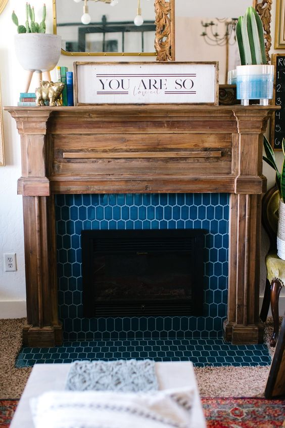 a faux fireplace with blue elongated hex tiles around and a rustic wooden mantel and frame for a farmhouse feel