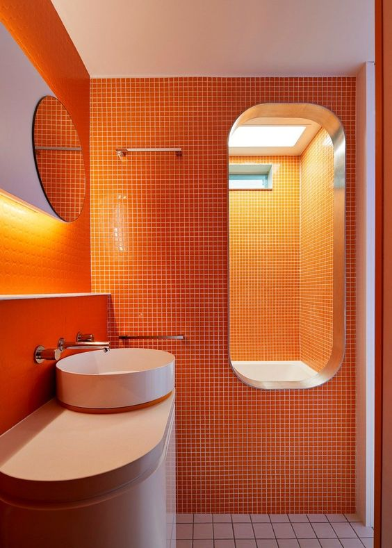 a super bright orange minimalist bathroom with white items to refresh the space and built in lights to make it even brighter