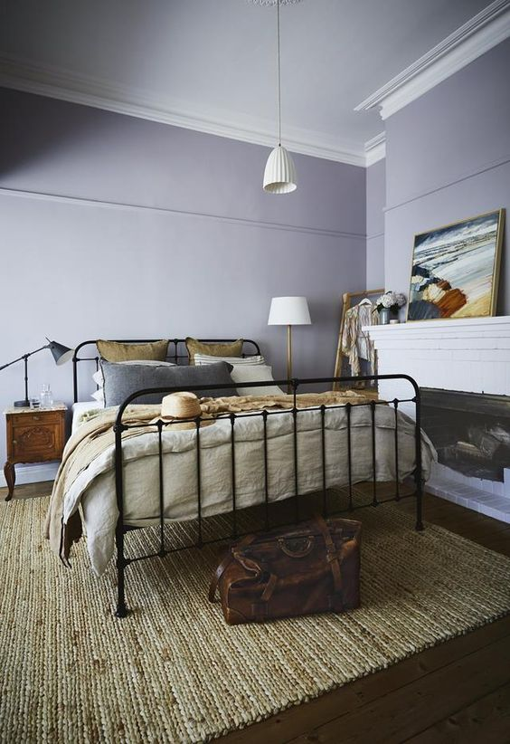 a vintage-inspired bedroom with lilac walls, a black forged bed, wooden nightstands, a fireplace and bold artworks