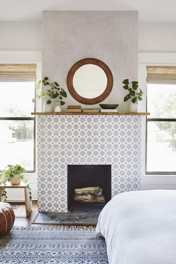 a faux fireplace with star print grey tiles around it and some stone on the floor looks very stylish