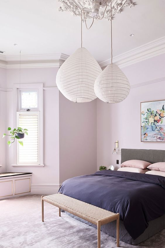 a welcoming modern bathroom with lilac walls, a grey bed with blush and navy bedding, paper lamps and a woven bench