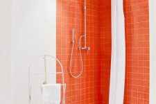 18 a contemporary bathroom with a shower space accented with bright orange tiles and butterfly tiles on the floor