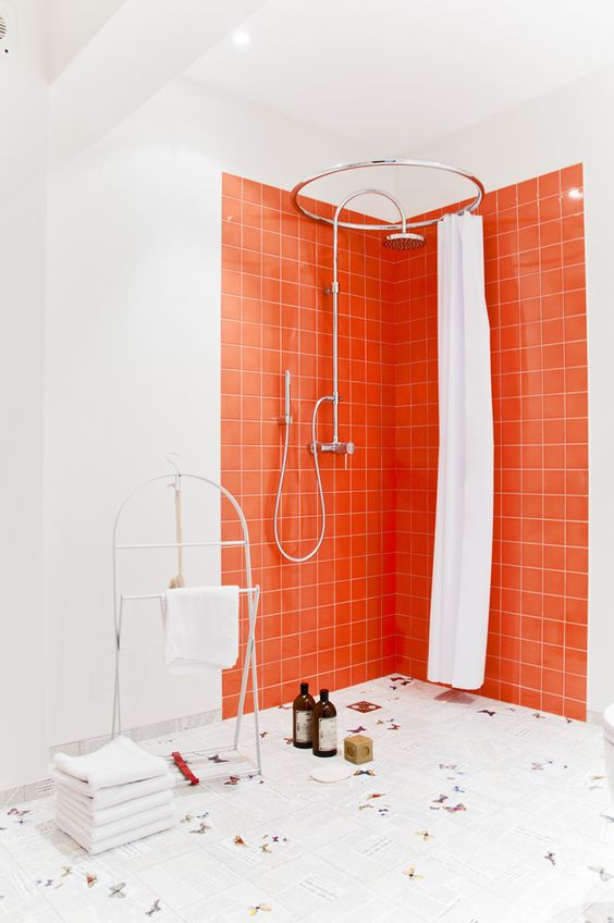 a contemporary bathroom with a shower space accented with bright orange tiles and butterfly tiles on the floor