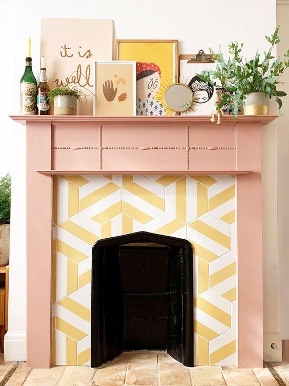 a faux fireplace with yellow and white graphic tiles around it and a peachy pink frame and mantel with a qurky gallery wall