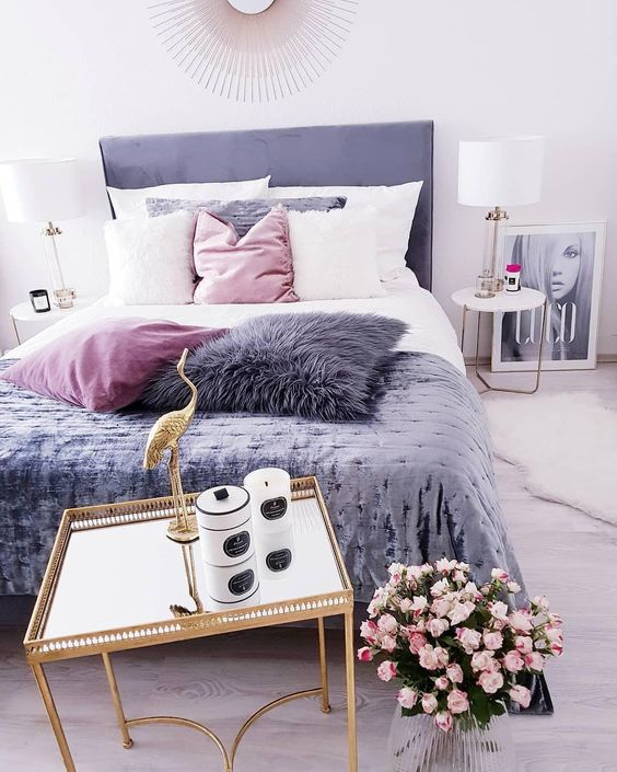 a gorgeous glam bedroom with a purple bed, a pillow and a blanket, touches of gold for a more chic feel