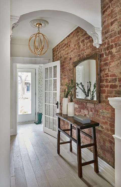lights wooden floors and an exposed brick wall create a chic and elegant space with a play of textures
