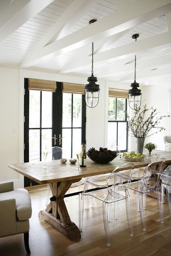 a cozy rustic dining space with acrylic chairs that help natural light go through and don't make the space dark