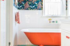 19 a fun bathroom with botanical wallpaper, white tiles and a bright painted floor plus an orange clawfoot tub