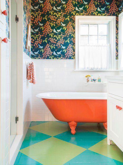a fun bathroom with botanical wallpaper, white tiles and a bright painted floor plus an orange clawfoot tub