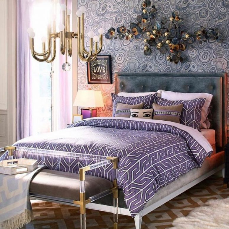 a maximalist bedroom with a printed accent wall, a bold artwork, a glam chandelier and a bench with gold touches and lilac and purple linens