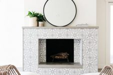 19 a neutral contemporary space with a fireplace clad with monochromatic patterned tiles and a laconic grey mantelw ith plants