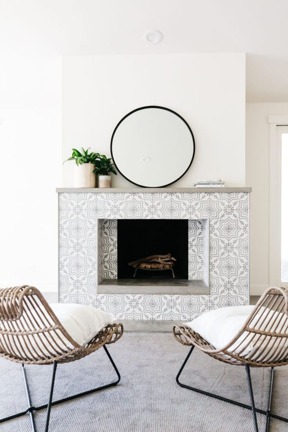 a neutral contemporary space with a fireplace clad with monochromatic patterned tiles and a laconic grey mantelw ith plants