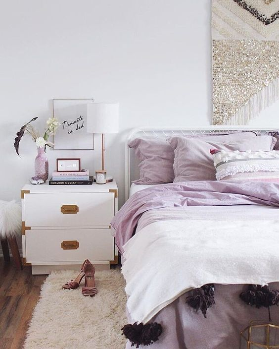 a modern glam bedroom done in white, with lilac bedding and accessories, with a sequin hanging and gold touches here and there