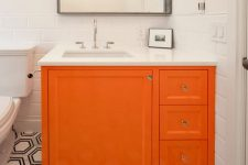 20 a monochromatic bathroom with a mosaic tile floor and super bright orange vanity that brings a touch of color to the space