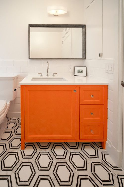 a monochromatic bathroom with a mosaic tile floor and super bright orange vanity that brings a touch of color to the space