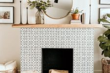20 a non-working fireplace with black and white geo tiles clad around and a light stained wooden mantel