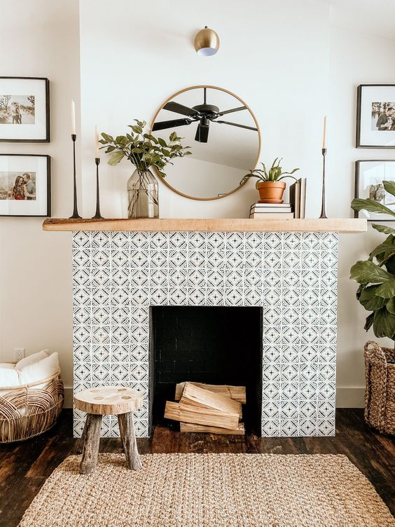 a non-working fireplace with black and white geo tiles clad around and a light stained wooden mantel