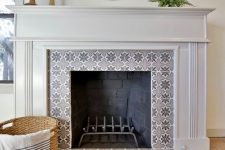 21 a non-working fireplace with grey star-patterned tiles around and on the floor and a refined white frame and mantel