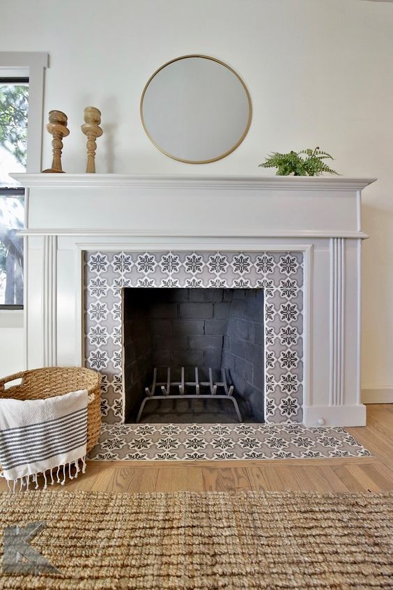 a non-working fireplace with grey star-patterned tiles around and on the floor and a refined white frame and mantel