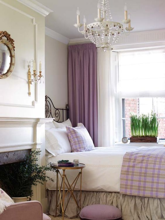 a sophisticated bedroom in neutrals, with a chic chandelier, a non-working fireplace, potted blooms and touches of lilac and purple