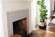 22 a real fireplace clad with star print grey tiles around it and with matte black ones on the floor plus a white frame and mantel