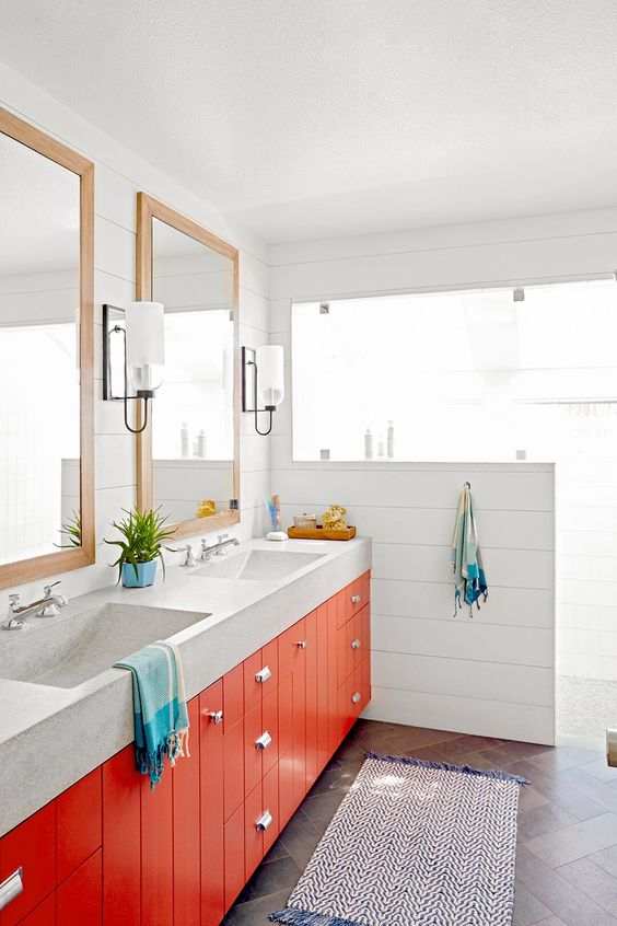 a stylish neutral bathroom spruced up with a bright orange double vanity and colorful textiles is super welcoming and cheerful