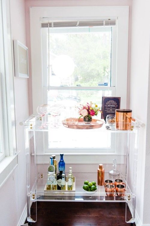 a lucite bar cart seems airy and floating in the air, it's perfect for a small nook and doesn't look bulky